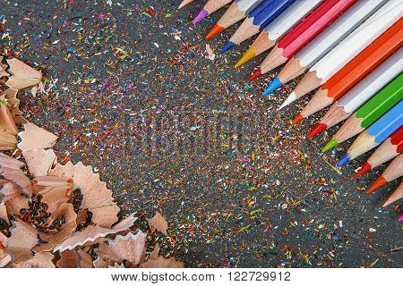 Close Up Shot Of Colored Pencil Crayons And Pencil Crayons Shavings On Dark Background