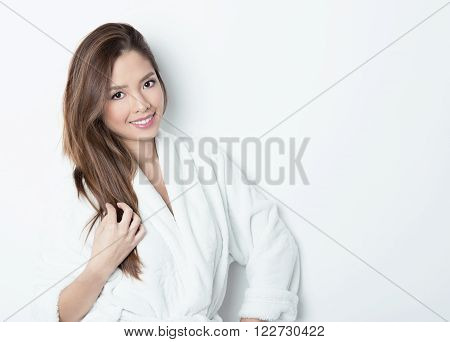 beautiful young asian woman with flawless skin and long hair posing in bath robe