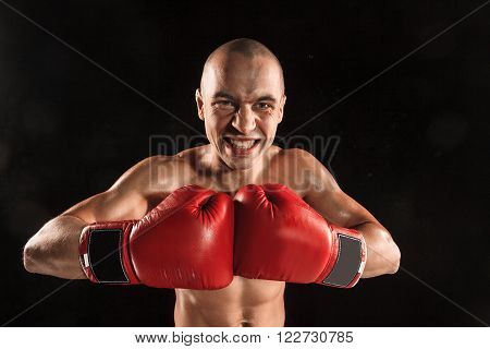 The young male athlete kickboxing on a black background  with screaming face. concept fury in the fight