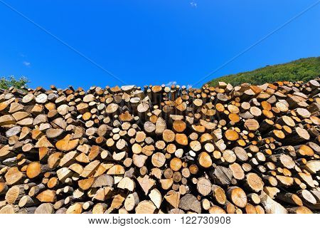 Dry chopped firewood logs in a pile on blue sky prepared for winter