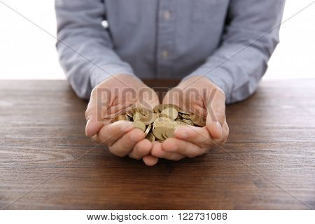 Man with handful of Ukrainian coins at wooden table on white background