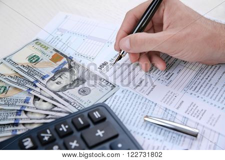 Man filling American form of Individual Income Tax Return at the table