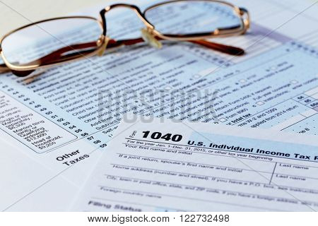 1040 Individual Income Tax Return Form with  metal rimmed glasses, close up