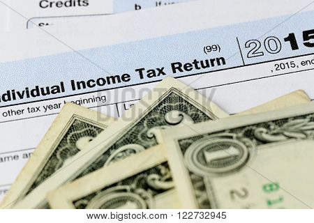1040 Individual Income Tax Return Form for 2015 year with one and two dollar bills, close up