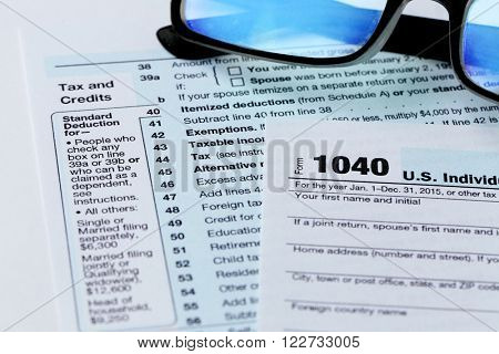 1040 Individual Income Tax Return Form with  black rimmed glasses on the white desk, close up