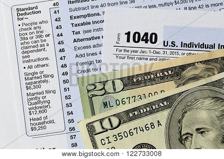1040 Individual Income Tax Return Form with twenty dollar bills on white background, close up