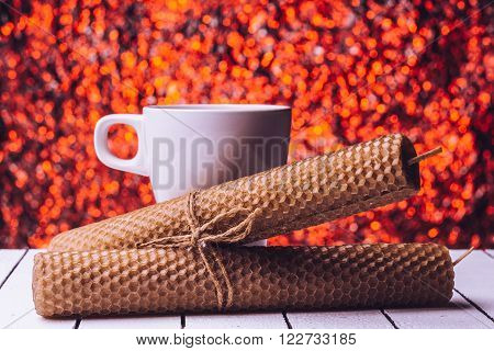 Beeswax candles and a cup of milk background bukeh
