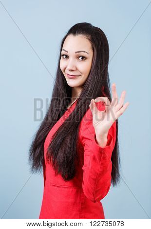 Young beautiful woman shows OK sign on the blue background