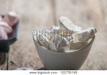 French meringue cookies on wooden background close up