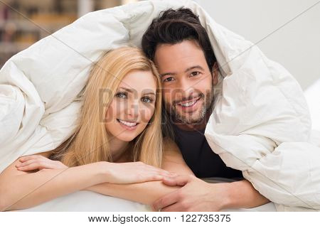 Cute romantic couple under a bed covers in the bed. Happy young couple lying down in their bed at home and looking at camera. Portrait of young couple having fun lying on bed at home.