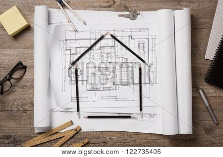 Top view of architectural blueprints, rolls and drawing instruments on the worktable. Shape of house with black pencils on a project house. Architectural drawings with house keys, new home concept.