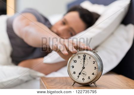 Young man being awakened by an alarm clock in his bedroom. Happy wake up of a man lying on the bed and stopping alarm clock. Man snoozing the alarm clock.