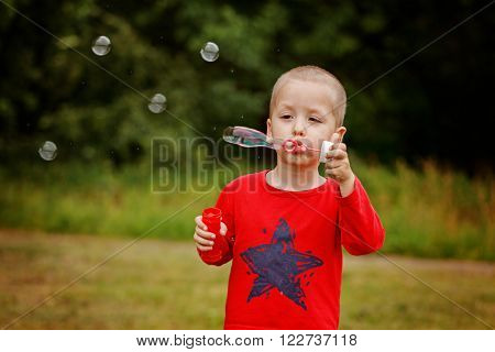 Child blowing a soap bubbles. Kid blowing bubbles on nature.
