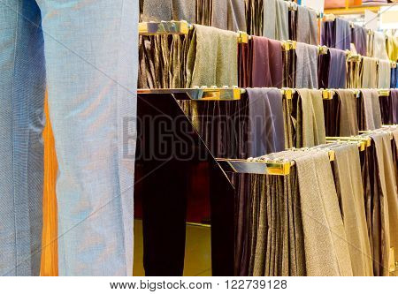 Supermarket display shelves in casual men's trousers