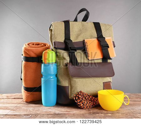 Tourism concept. Backpack, rug and plastic thermos on wooden table against grey background