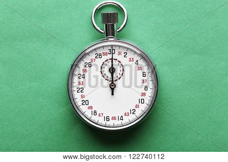 Stopwatch on green  background, close up
