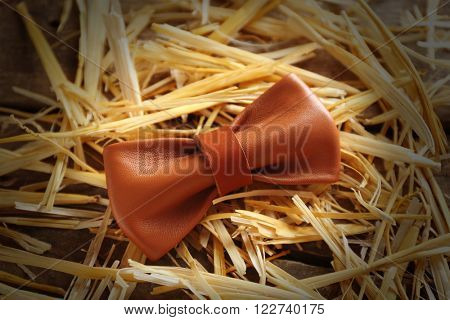 Light-brown leather bow tie on a thatch, close up