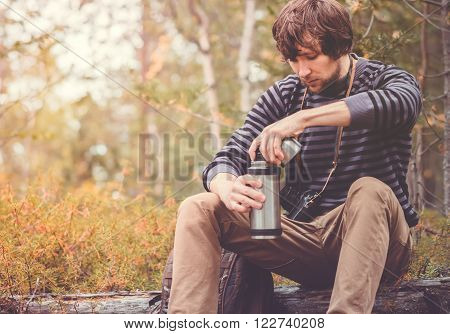 Traveler Man relaxing in forest with thermos backpack and photo camera Travel Lifestyle concept vacations outdoor