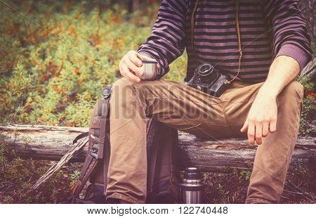 Traveler Man relaxing in forest with photo camera backpack and thermos drinking tea Travel Lifestyle concept Summer vacations outdoor