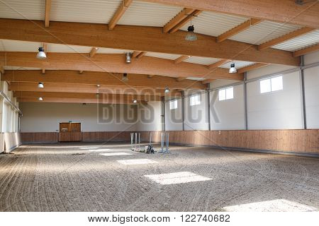 The empty bright manege for equestrian training indoor