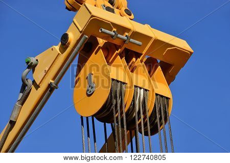 A pulley with steel cables in tension and yellow frame at work in construction site