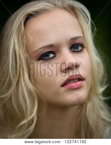 Outdoor natural light portrait of a beautiful teenage blond girl with heavy eyeliner glossy lips and pink mascara.