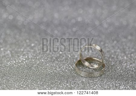 Soft focus of 2 silver rings on gray glittery background with shallow depth of field and copyspace