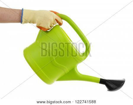Female hand in a glove holding a big green with black spout watering can isolated on white background