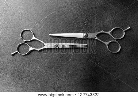 Professional metal scissors lying in two different positions on the grey surface, top view