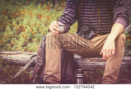 Traveler Man relaxing in forest with photo camera, backpack and thermos drinking tea Travel Lifestyle concept Summer vacations outdoor