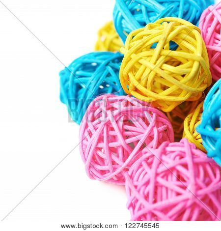 Pile of decorative colored straw balls isolated over the white background, close-up fragment crop as a copyspace backdrop composition