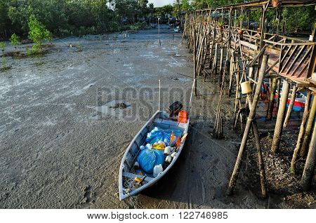 fishing sampan stranded near to wooden pier in Asia
