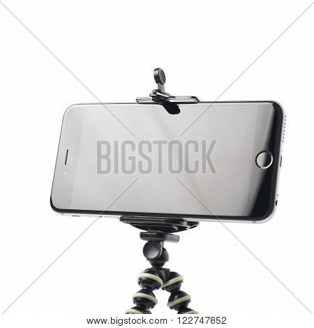 Smartphone set up on a tripod isolated over the white background