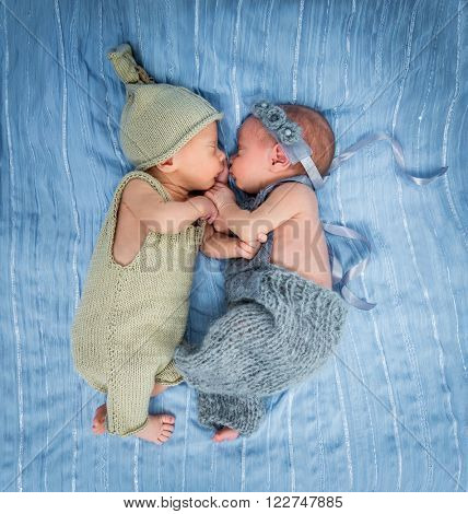newborn twins - a boy and a girl sleeping on a blue blanket