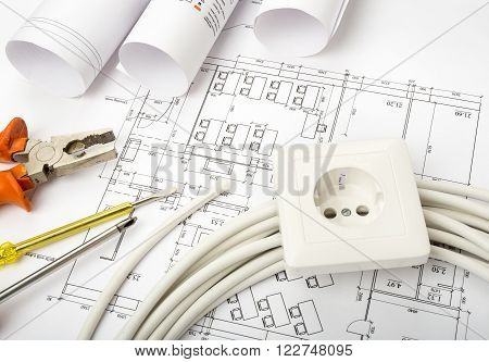 Architecture plan and rolls of blueprints with cable and socket. Building concept
