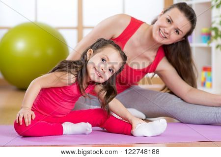 Portrait of child girl and her mother doing physical exercise at home