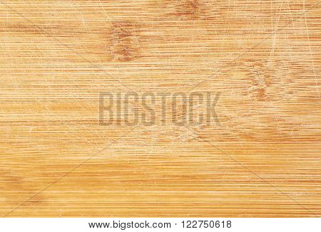 Fragment of a well-used wooden cutting board, close-up fragment as a background texture