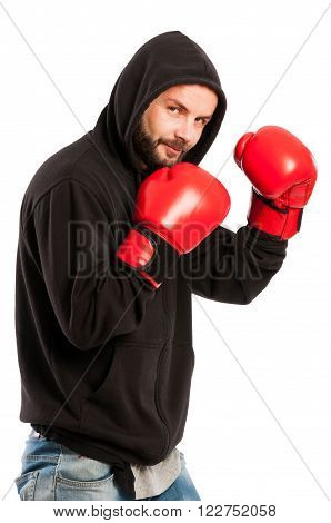 Amateur boxer wearing a black hoodie and red gloves on white background