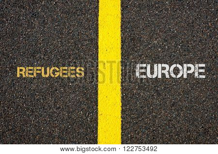 Antonym concept of REFUGEES versus EUROPE written over tarmac, road marking yellow paint separating line between words