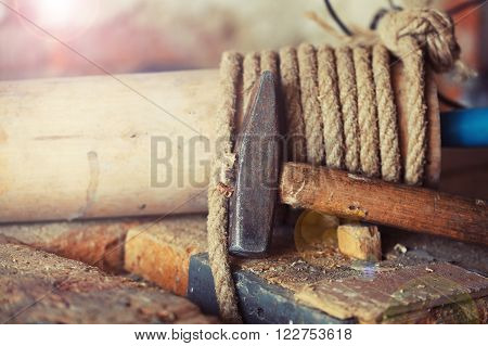 Hammer on the crafting table. The concept workplace of carpenter
