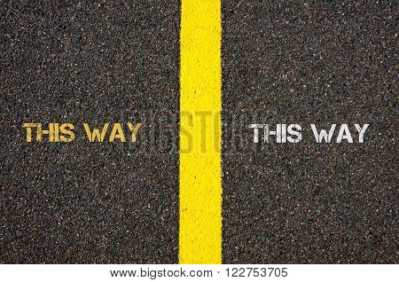 Antonym concept of THIS WAY versus THIS WAY written over tarmac, road marking yellow paint separating line between words