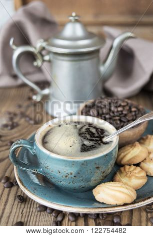 Blue cup of black coffee biscuits and coffee pot surrounded by linen cloth sugar pieces and coffee beans on old wooden table