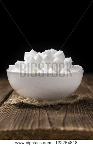 Bowl with white Sugar (selective focus; close-up shot) on a vintage wooden background