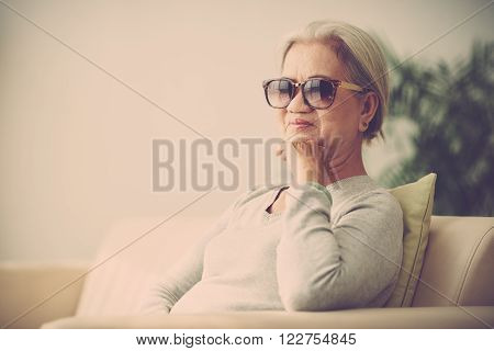 Senior woman in sunglasses sitting on the sofa