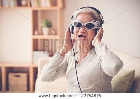 Mature woman in funny sunglasses  and headphones singing a song