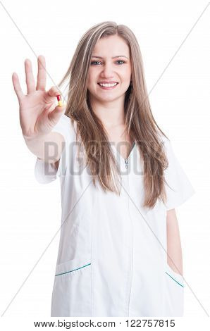Friendly And Attractive Nurse Holding One Antibiotic Pill