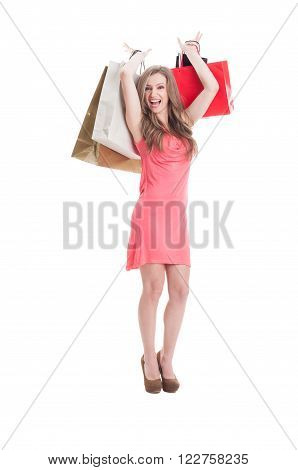 Excited and carefree shopping female holding shopping bags in the air
