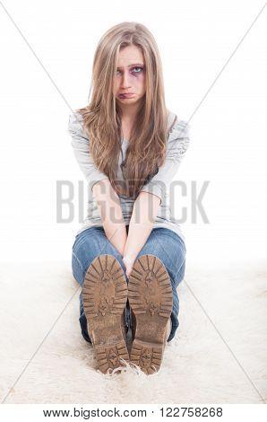 Sad woman victim of domestic violence sitting injured on the floor