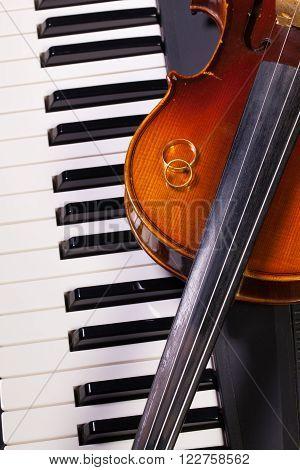 Detail of piano keyboard old violin and wedding rings