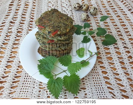 Potato with nettles fritters on a plate with Melissa cooking food for a vegetarian diet with nettles and quail eggs